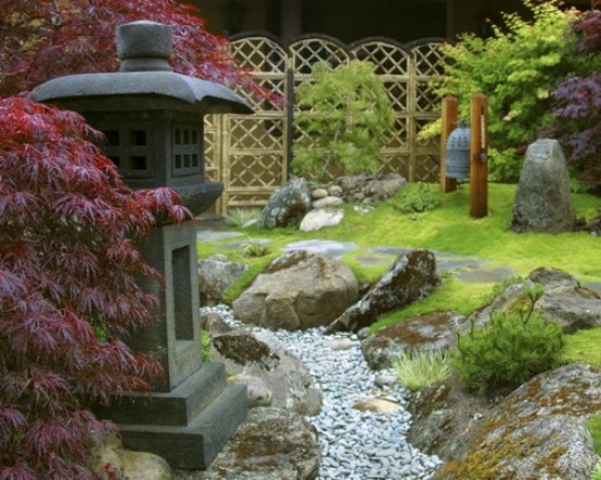 green grass, pebbles, rocks, red maples, a stone lantern and a large bell create a very beautiful and zen-like look