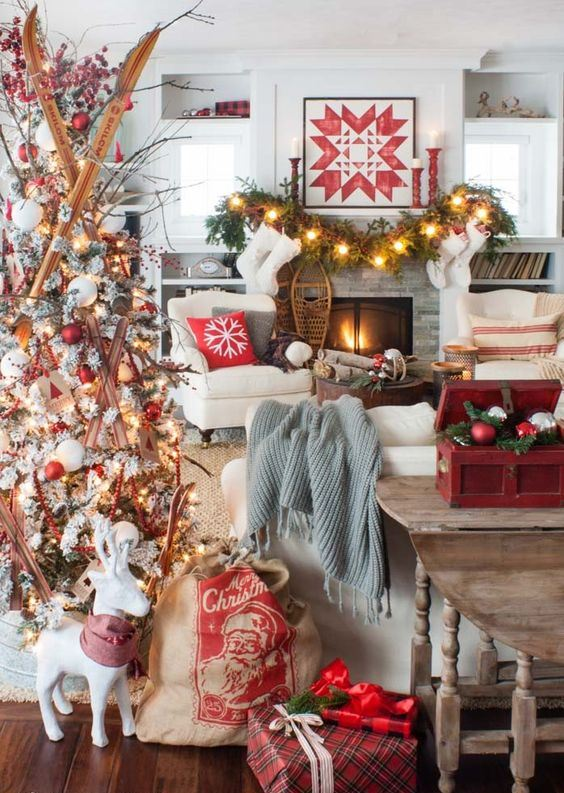 a bold and creative Christmas living room with a white tree with red and white ornaments and skis, a fir garland with lights, red candleholders and a red box with ornaments