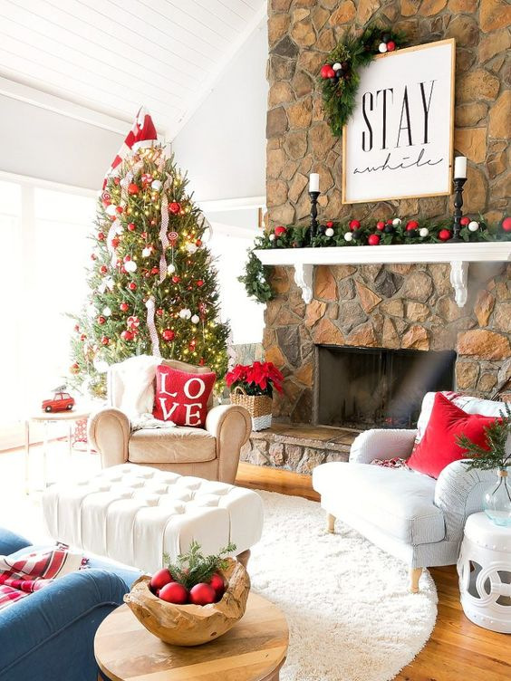 a bright holiday living room with a Christmas tree decorated with red and white ornaments, with a matching garland, red pillows and ornaments