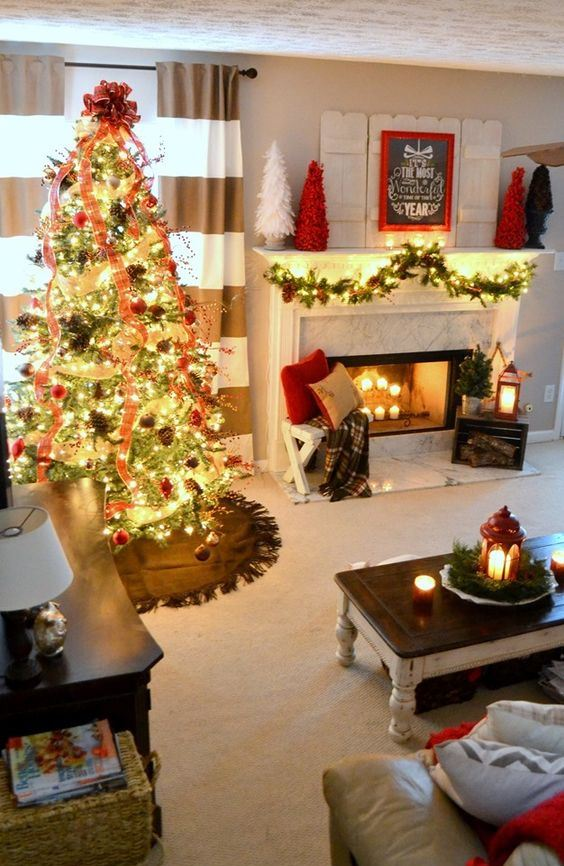 a cozy Christmas living room with a fir garland with lights, bright mini trees, a red lantern, a Christmas tree with lights, red ribbons, pinecones and red ornaments