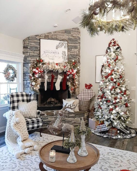 a farmhouse Christmas living room with a flocked Christmas tree with lights and white and red ornaments, a flocked garland with ornaments