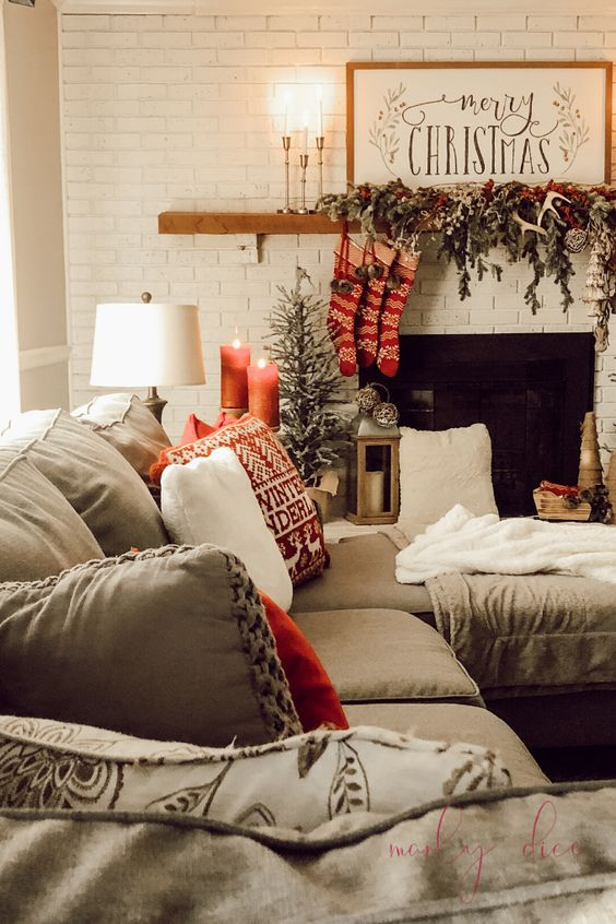 a cozy Christmas living room with fir branches, berries, antlers and red stockings on the mantel, red candles and printed pillows
