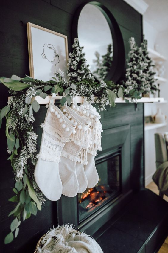 a greenery garland with flocked mini trees and white boho sotckings with fringe for elegant natural decor