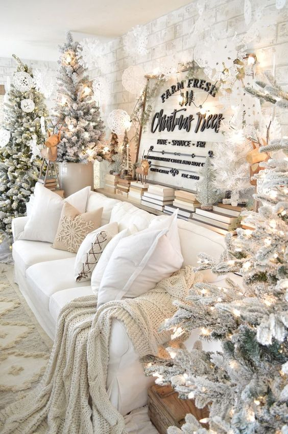 a winter wonderland living room with several flocked Christmas trees with lights, some more mini trees and lots of white paper snowflakes