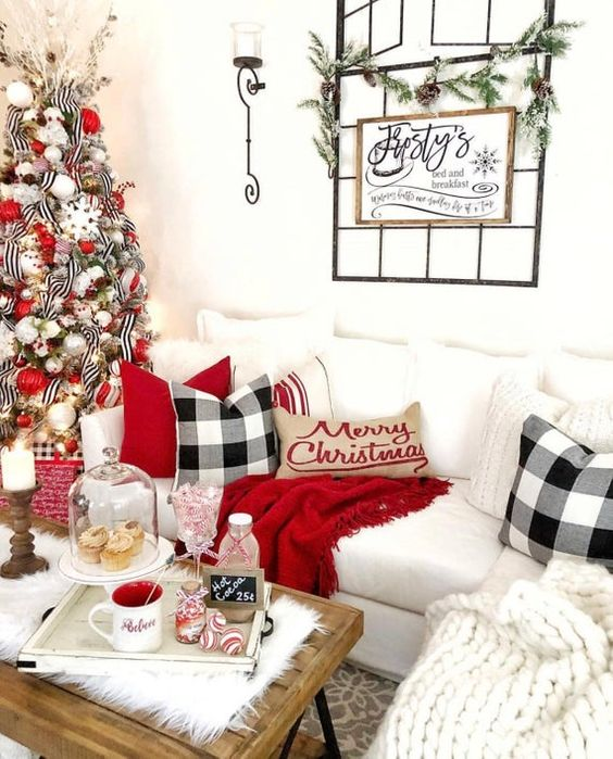 bright and fun Christmas decor with a white chunky blanket, plaid pillows, red touches, a greenery garland, a Christmas tree with white, red and silver ornaments