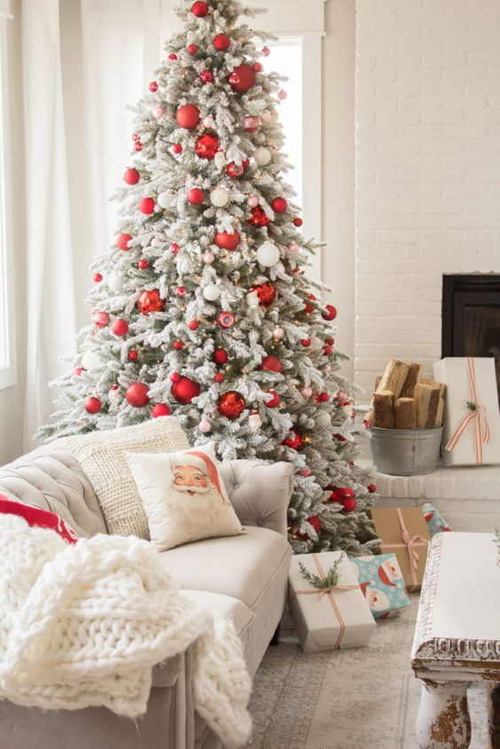 a flocked Christmas tree with red and white ornaments, a printed pillow and a white chunky knit blanket for a cozy feel