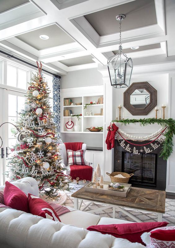 cozy and chic Christmas living room decor with red pillows, bead and pompom garlands, a fir garland, a flocked Christmas tree with lights, snowflakes and letters