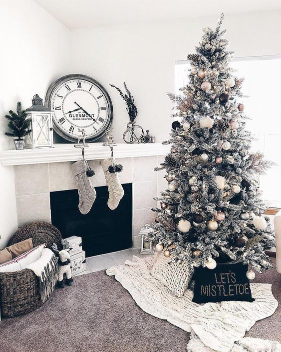 gorgeous monochromatic Christmas decor with a flocked Christmas tree with gold, black and white ornaments, knit stockings, mini trees and chunky blankets