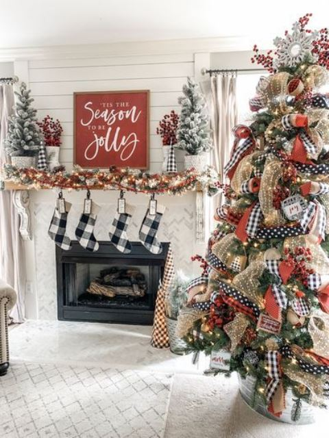 farmhouse Christmas decor with plaid stockings, a fir garland with lights, flocked mini trees and a large on with lights and printed ribbons