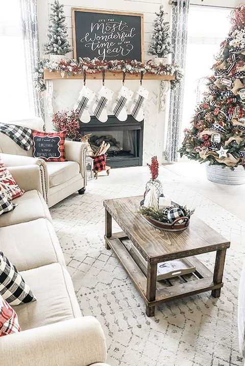 plaid farmhouse Christmas decor with plaid pillows, flocked garlands and flocked Christmas trees decorated with ribbons