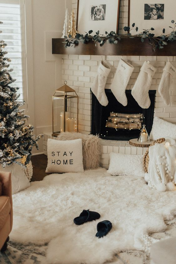 cozy winter holiday decor with white faux fur, white pillows and blankets, a greenery garland, white sotckings and a flocked Christmas tree