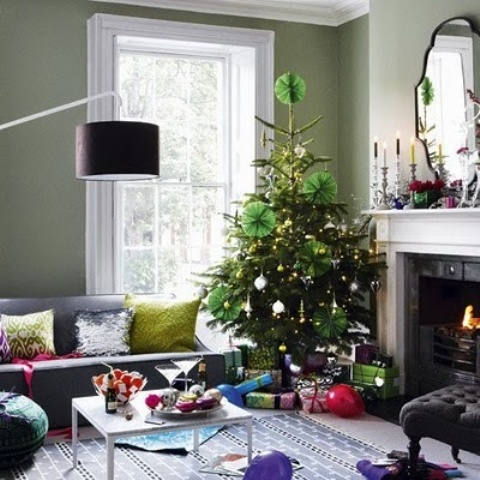 a contrasting living room with bright touches and a Christmas tree with lights, metallic ornaments and green paper ornaments is very chic and cool