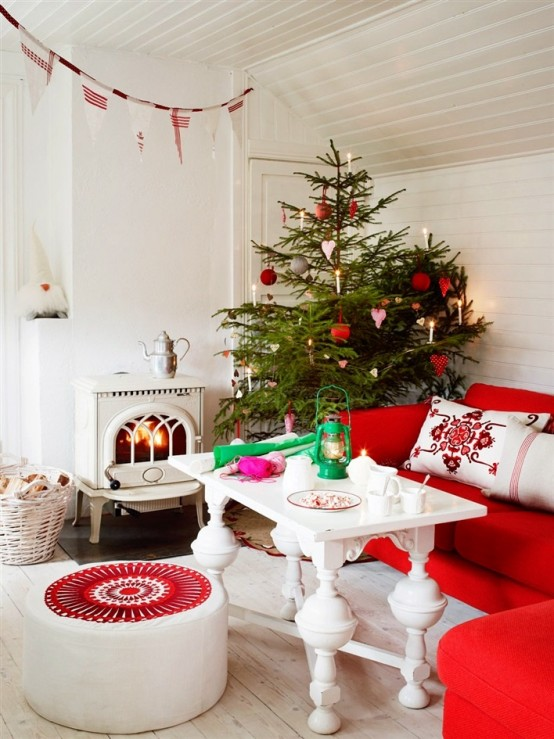 a red and white Scandinavian Christmas living room with matching holiday decor - a Christmas tree with red and white ornaments, a red and white fabric banner over the space