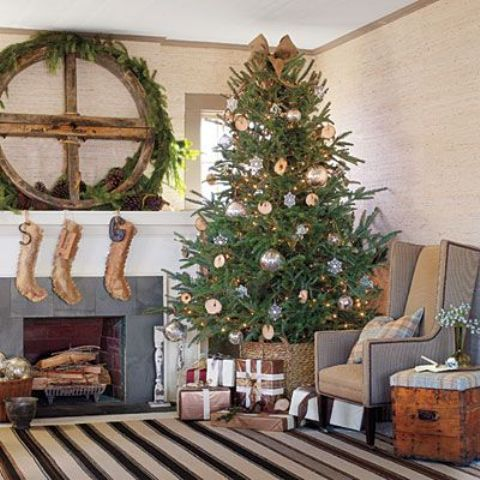 an oversized fir branch wreath, burlap stockings, a Christmas tree with metallic ornaments in a basket for a rustic holiday feel in the space