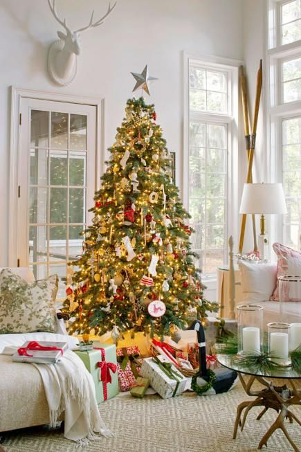 a Christmas tree with lights, red and white ornaments and some gifts under it is very bright and sets the tone in the space