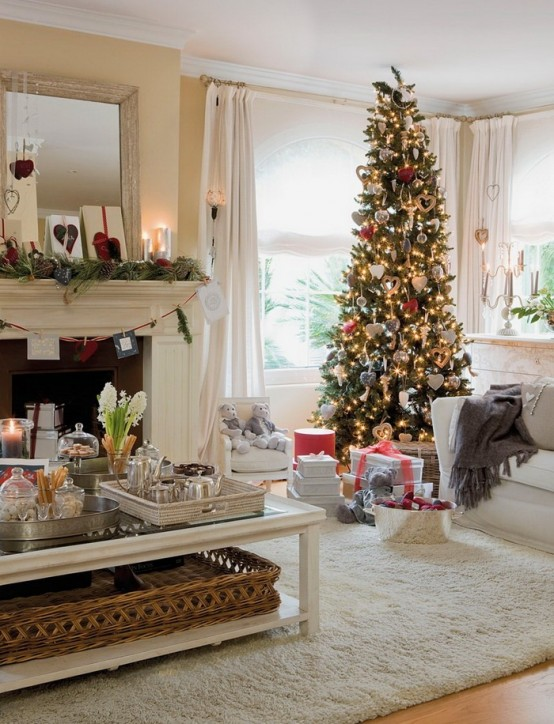 a fir garland with pinecones, a Christmas tree with lights, red and white ornaments create a holiday ambience in this living room