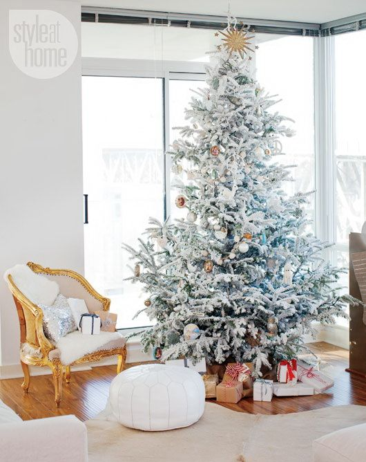 a flocked Christmas tree with silver and copper ornaments and white and silver sequin pillows for cozy holiday decor