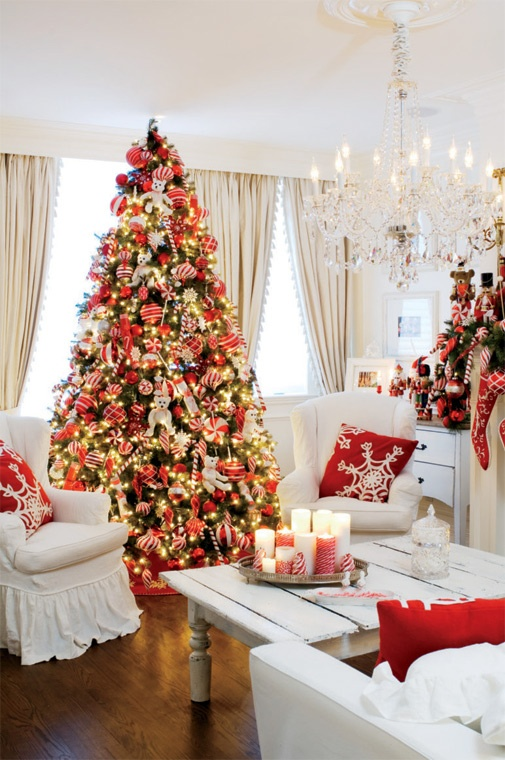 a super bold red and white Christmas living room with a bright Christmas tree with lights and red and white ornaments, stockings, pillows and a garland with bright red decor