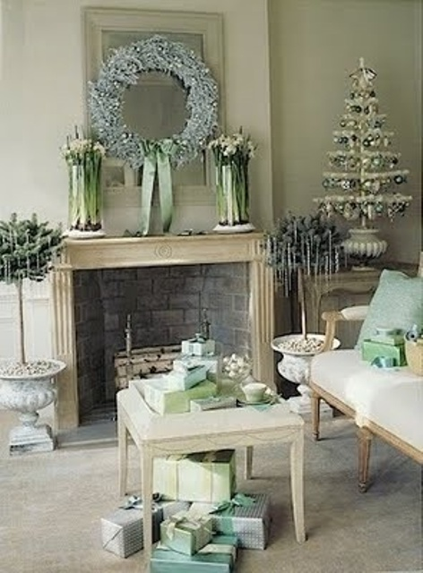 a pastel vintage living room with refined vintage holiday decor - a small tabletop tree with green and silver ornaments, a frozen light blue wreath and potted plants with icicles hanging on them