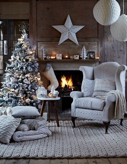 a frozen living room with a fireplace, a frozen Christmas tree with lights and metallic ornaments plus giant stars
