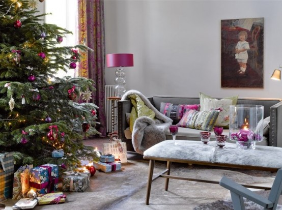 a Christmas tree decorated with fuchsia and purple ornaments, with lights and touches of purple here and there