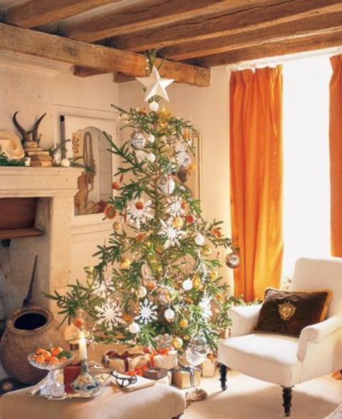a Christmas tree with white and metallic ornaments, with dried citrus and snowflakes and stars is lovely and creates a mood here