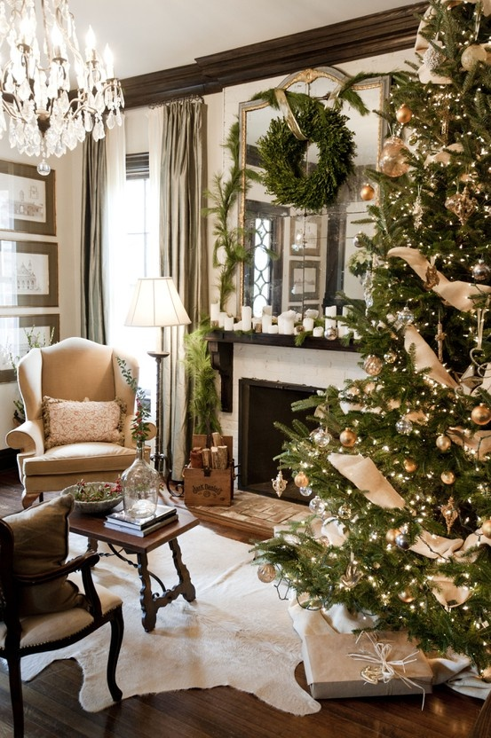 an evergreen wreath, lots of candles and ornaments on the mantel and a Christmas tree decorated with lights, gold ornaments and burlap ribbons for a festive feel in the space