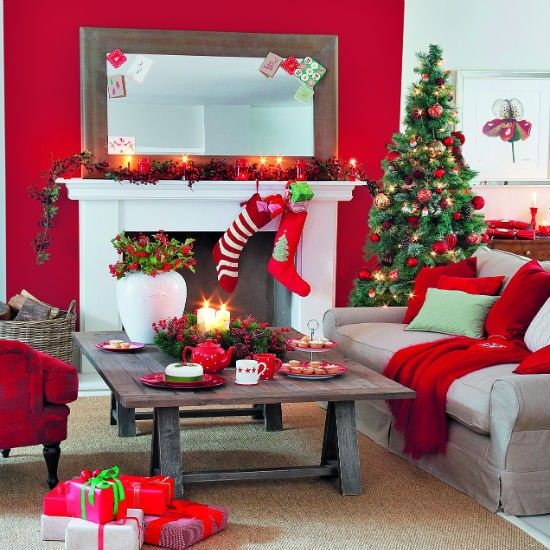 a bright red and neutral Christmas living room with a greenery and berry garland on the mantel, funny red stockings, a Christmas tree with lights and red ornaments, red pillows and blankets plus red teaware on the table