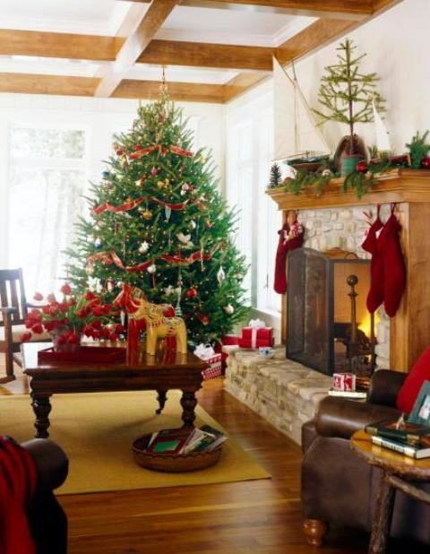 a bold red and white Christmas tree with red and white ornaments, red stockings, a fir garland with red ornaments and a potted tree