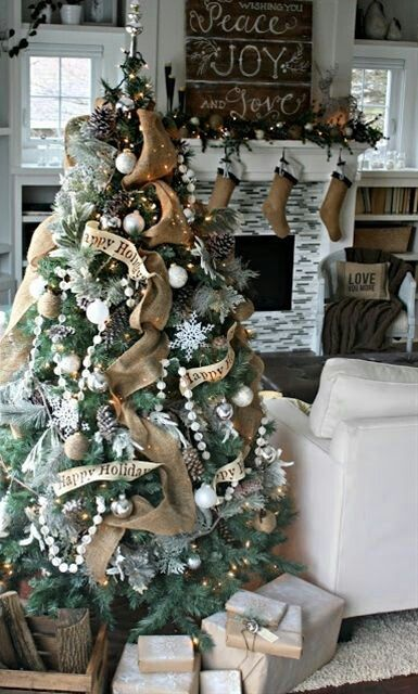 burlap stockings, a fir garland with silver ornaments, a Christmas tree with burlap ribbons, pompoms, silver and white ornaments for a rustic holiday feel in the room