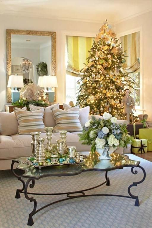a tray with colorful ornaments, metallic candleholders, a Christmas tree with lights, metallic and white ornaments for a holiday feel in the space