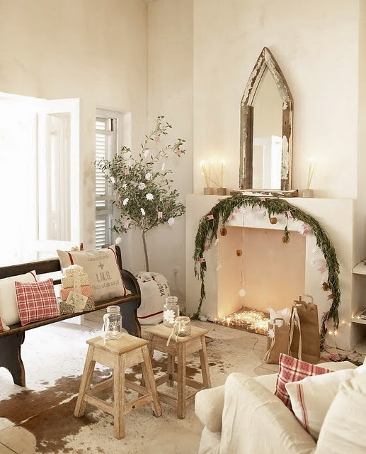 plaid pillows, some lights in the fireplace and a fir garland with ornaments make the Mediterranean space look very holiday-like