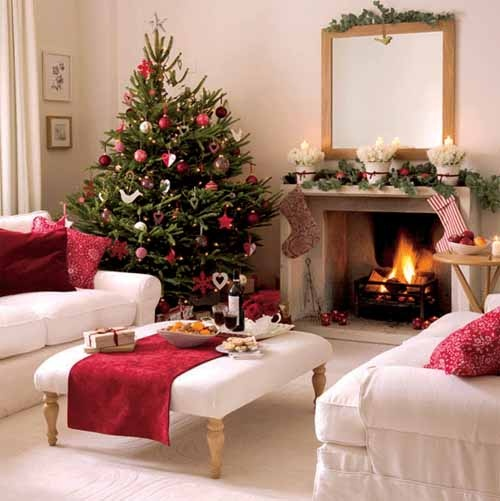 refined neutral Christmas living room with a tree decorated with red and white ornaments, stockings, colorful pillows and other stuff