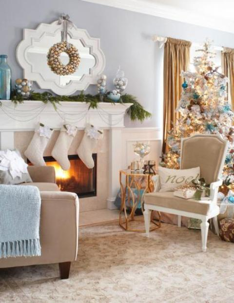 white stockings, beads, fir garlands on the mantel, a gold ornament wreath, a flocked Christmas tree with blue and gold ornaments for refined holiday decor