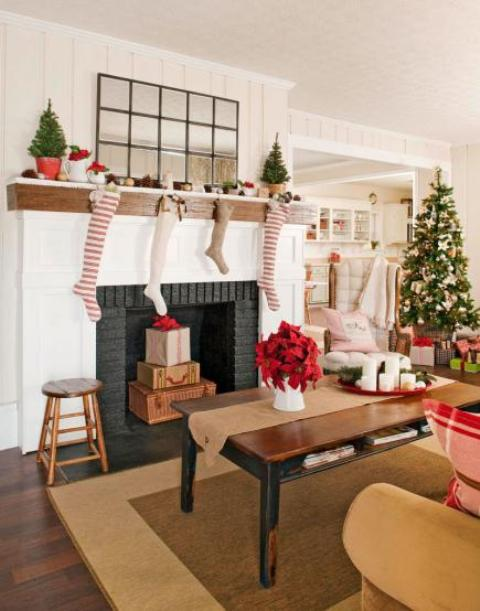 striped, white and burlap stockings on the mantel, mini Christmas trees in baskets, a Christmas tree with vine and green ornaments for holiday cheer
