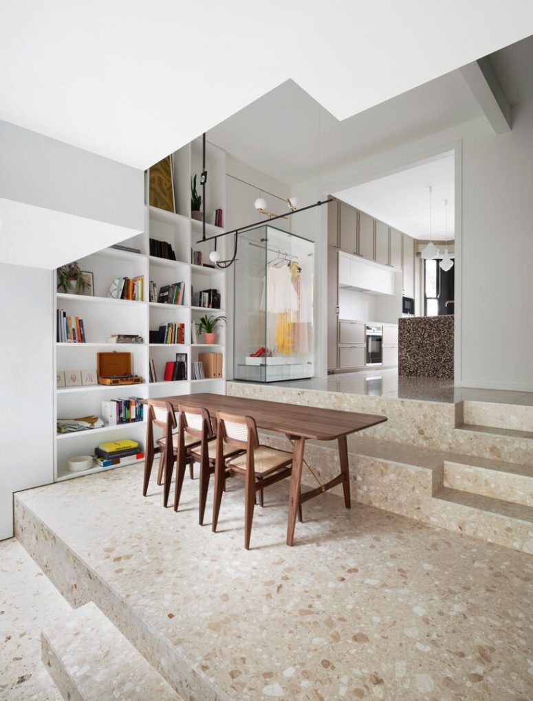 There's a large open shelving unit built-in on the left, a cozy wooden dining set on the steps