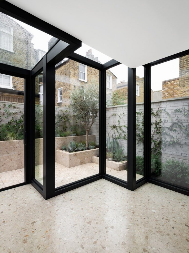 Glass walls offer much natural light and cool views of a private garden clad in terrazzo