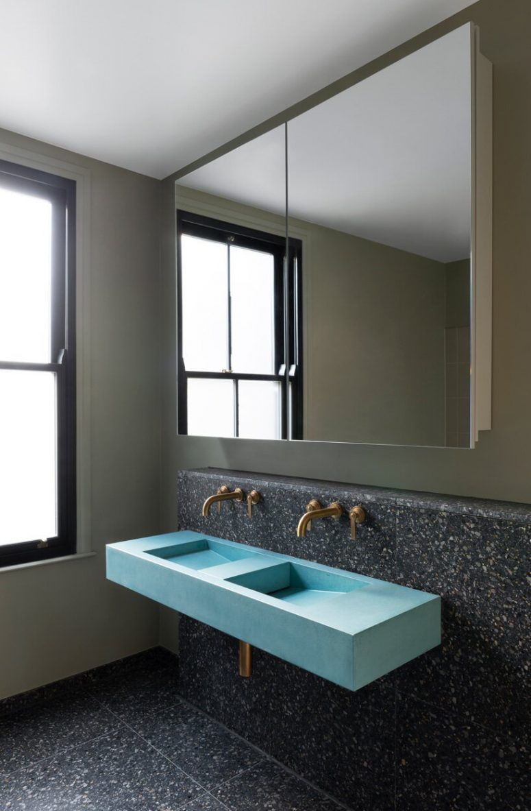 The bathroom is done wiht dark terrazzo tiles, a blue double sink