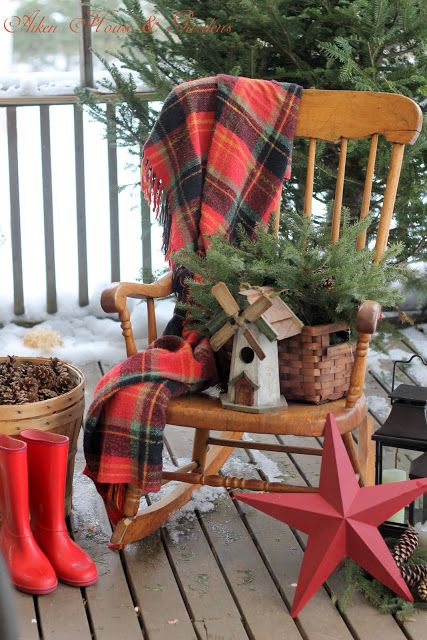 a vintage rocker, a plaid blanket, a basket with fir branches, a mini mill, a red star and boots for a rustic feel outdoors