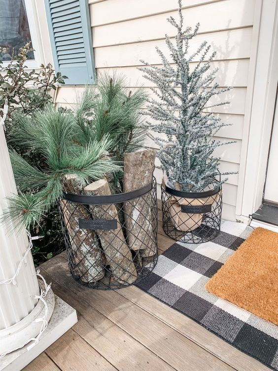 a wire basket with firewood and fir branches and a basket with a flocked Christmas tree for a slight rustic feel in the porch