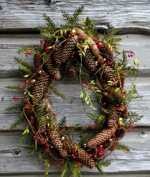 a rustic Christmas wreath of pinecones, greenery and berries is a cozy rustic decor idea for your front door