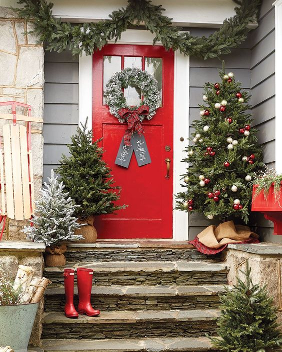 bright Christmas front porch with mini trees in burlap and a tree with red and white ornaments, red boots, a flocked wreath and a fir garland