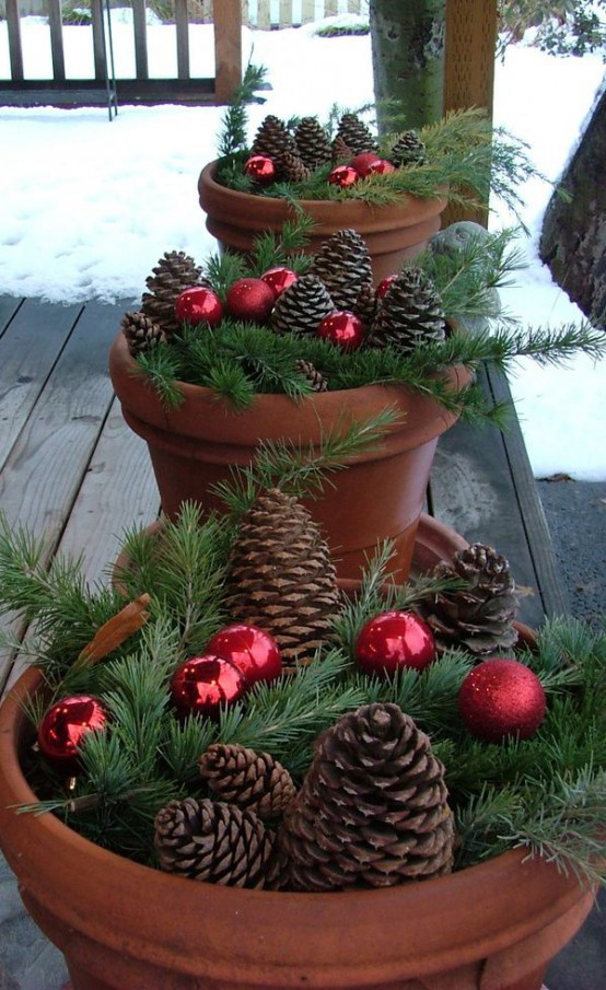 terracotta pots with fir branches, pinecones and red ornaments will make your front porch amazingly rustic and very chic
