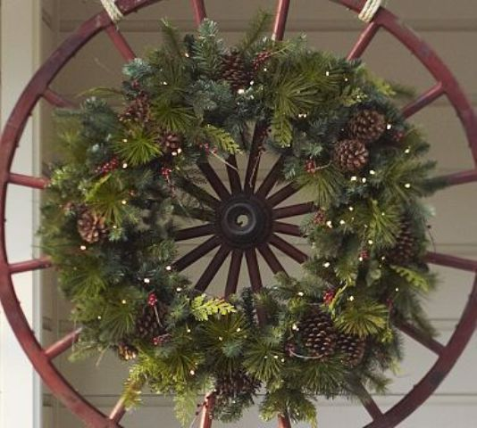 a wheel with a fir branch wreath, berries and lights for a cool rustic feel in your outdoor space