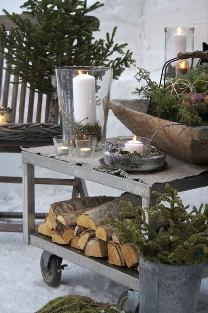 Nordic Christmas decor with firewood, fir branches, moss, candles is a great idea for a rustic and all-natural feel in your outdoor spaces