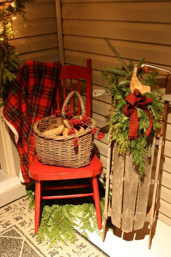a red chair with a red plaid blanket, a basket with pinecones and berries, a wooden sleigh with a plaid bow and fir branches