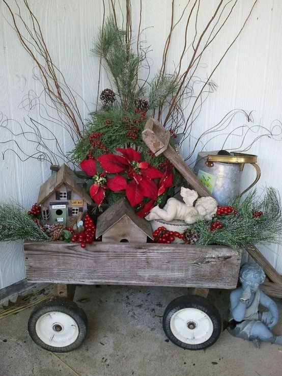 a wooden cart with berries, greenery, red blooms, branches, mini houses and a bucket will make your front porch rustic and cozy
