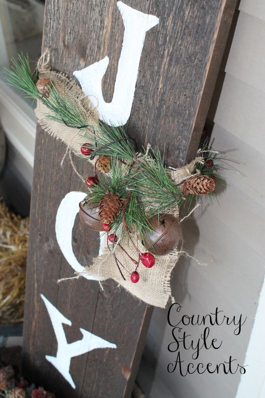 a wooden JOY sign with a burlap bow, fir branches, berries, bells and pinecones is a lovely and easy rustic decor idea