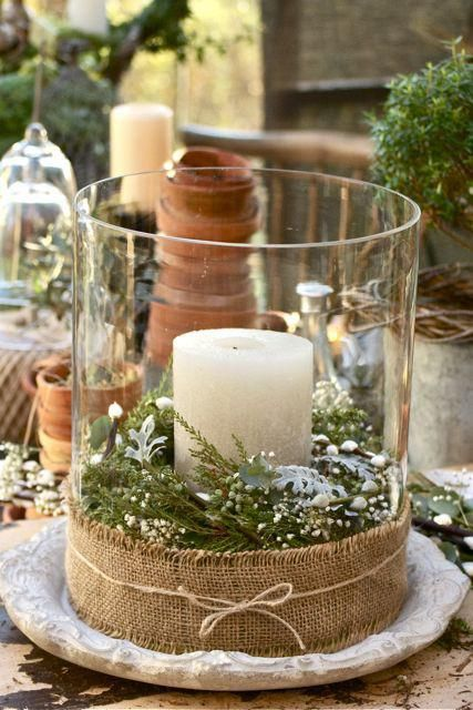 a glass jar with greenery and fir, with burlap around and a large candle can be used both indoors and outdoors