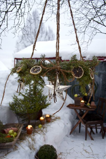 a rustic chandelier of fir branches, dried citrus slices and stars is a fantastic outdoor decoration you can DIY